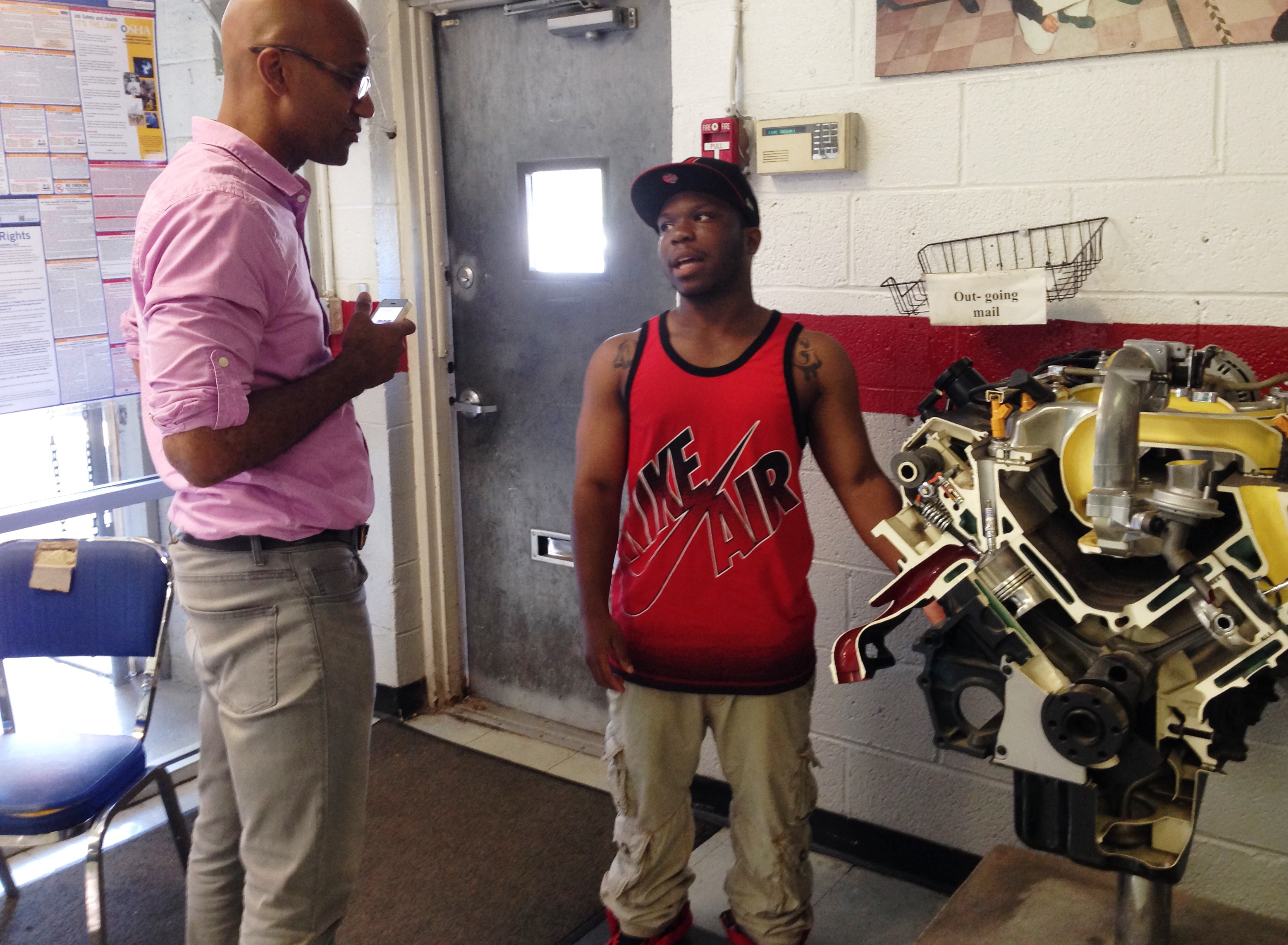 Dorian Moody, right, a recent student of NCC's Automotive Technician Employment and Training Program, speaks with Colorlines reporter Kai Wright, left.