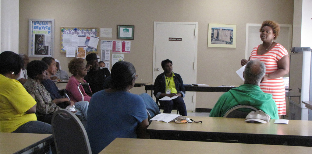 Aquilla Lowery, standing far right, an outreach navigator at the Hyacinth AIDS Foundation, spoke to New Community Gardens Senior residents about how to prevent HIV.