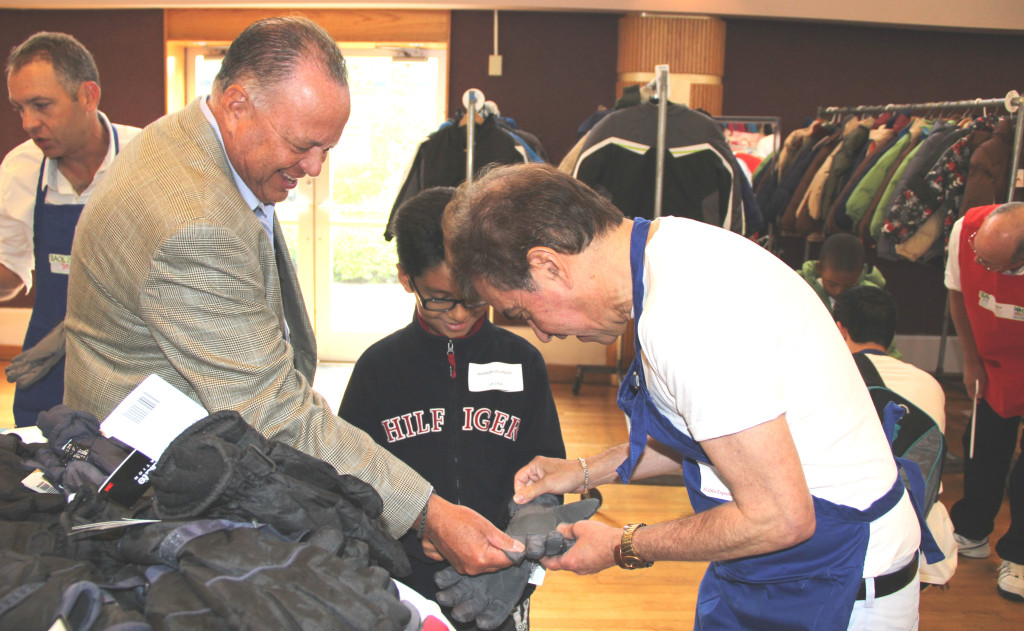 James R. Gonzalez, President and CEO of University Hospital (l), and a NCJW/Essex volunteer (r) help a youngster select winter gloves at the Back 2 School Store.