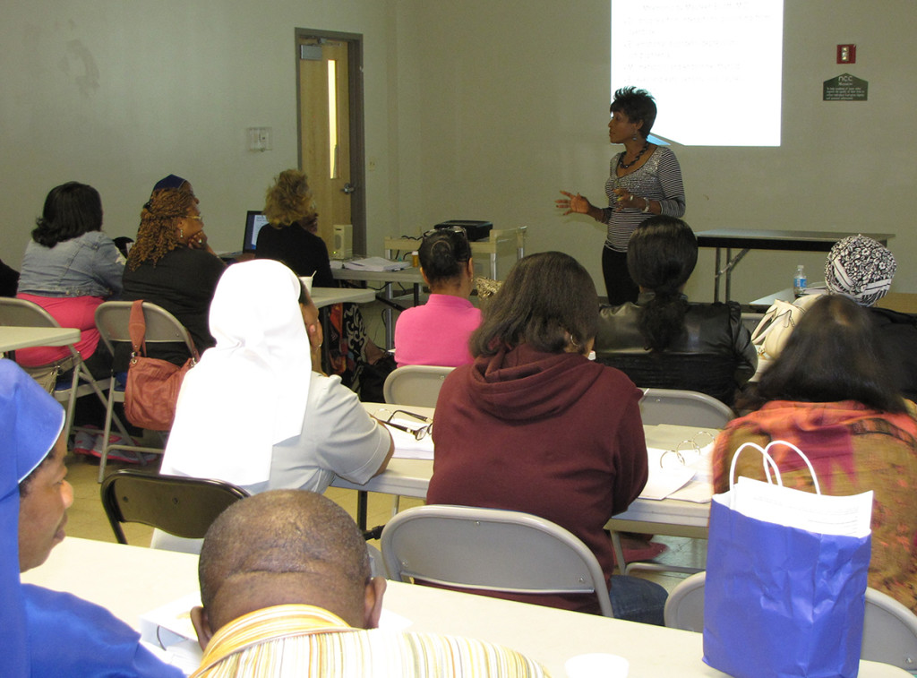 NCC Director of Nursing Veronica Onwunaka, standing, leads a seminar on how NCC caregivers can identify signs of dementia and assist NCC seniors facing the degenerative brain condition.