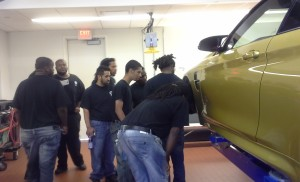 NCC automotive trainees inspected a vehicle undergoing repair at the BMW shop. In addition to BMW, NCC partners with other automakers, such as Ford, and local employers, to place trainees in internships as part of the Automotive Technician Employment and Training Program.