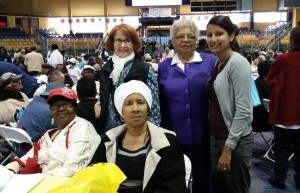 Care Coordinator Jasminee Sawh-Ramroop, right, and four seniors from New Community, participated in health screenings and exercise demonstrations. Seniors also received bagged produce from a farmers market and free admission to Turtle Back Zoo.