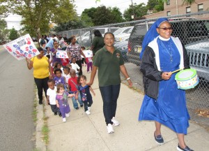 Led by Sister Maurice Okoroji, right, Director of Harmony House Early Learning Center, the students and staff waved flags, held banners and marched on the sidewalk. Okoroji said it's important to teach the younger generations who weren't born then about both the lives lost and the heroism displayed on that day.