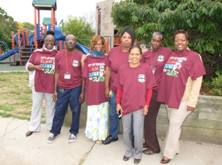 """New Community is supporting the City of Newark's effort to clean up and beautify its neighborhoods as part of a campaign called """"Slam Dunk The Junk."""" From left, Harmony House staff Linda Washington, Terrence Dhainy, Lisa Chavis, Carolyn Andrews, Melvina Coleman, Angela Hall and Angela Potts don t-shirts provided to NCC by the city that promote removing trash from the streets and planting flowers."""
