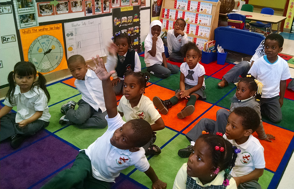 Gregory, seated in front raising his hand, has made strides in his personal and educational development at NCC Community Hills Early Learning Center.