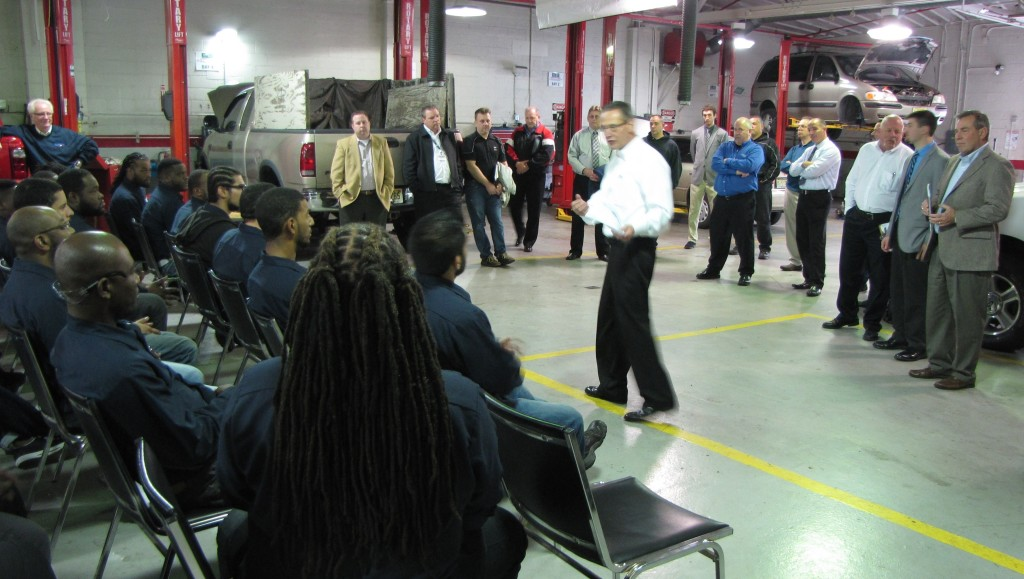 About 20 representatives from Ford Motor Company came to New Community's Automotive Training Center to speak with students training to become automotive technicians about job opportunities at their sites as well as overall demand for skilled labor in their industry. Standing in the center is Roy Gadomski, Parts and Service Operations Manager of the New York Region of Ford.
