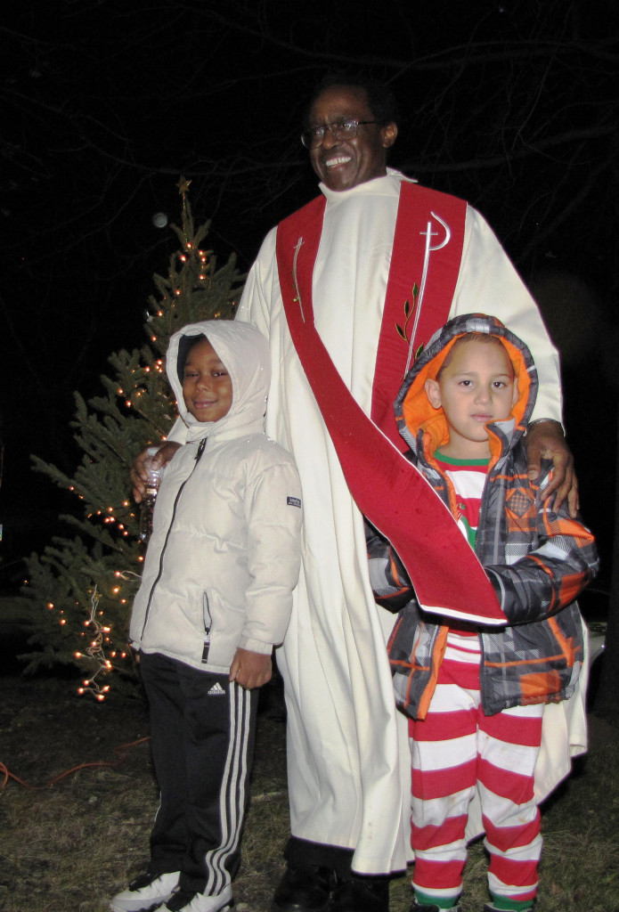 "Father Beatus Kitururu, standing center, blessed the Christmas tree and reminded those in attendance of the spiritual symbolism of light. ""Where there is light, there is love and forgiveness,"" he said."