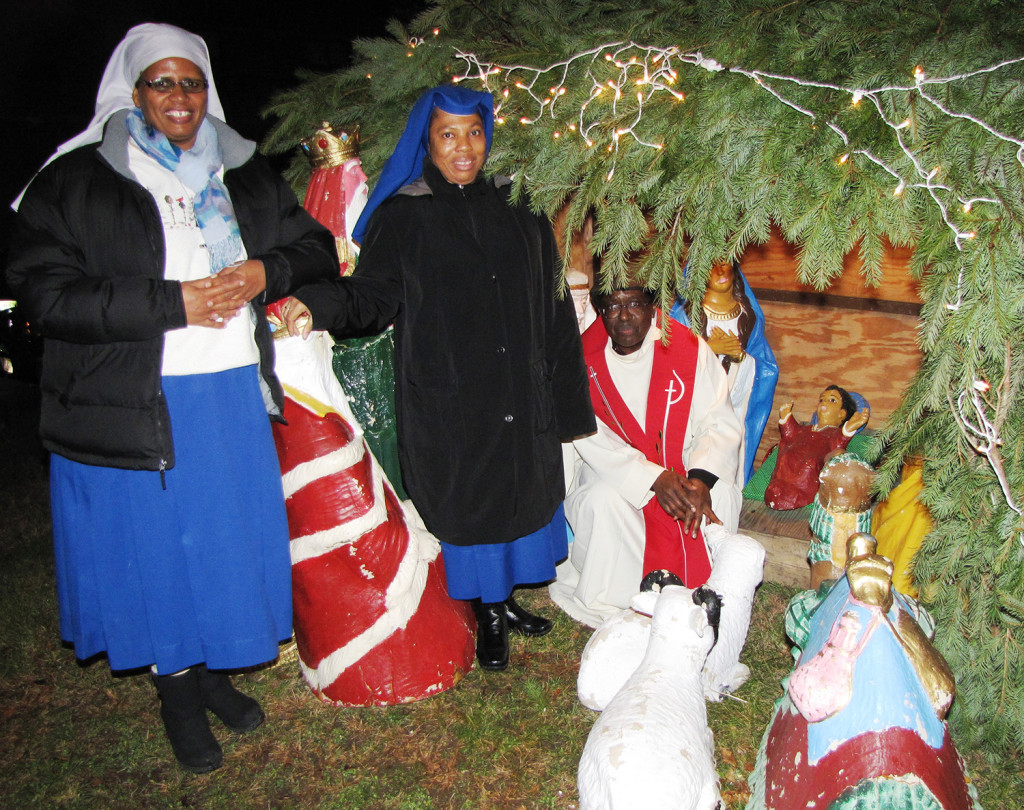 From left: Sister Theresia Hhayuma, Sister Mary Prisca and Father Beatus Kitururu gathered with residents of NCC Manor Senior for the crib blessing at the nativity scene displayed in front of 545 Orange St. in Newark.