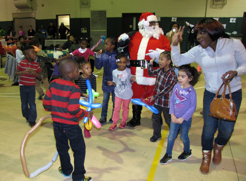 More than 200 children and their parents came to the Neighborhood Center on Hayes Street on the Saturday before Christmas for a complimentary breakfast and family photograph with Santa. Each child also received a gift.