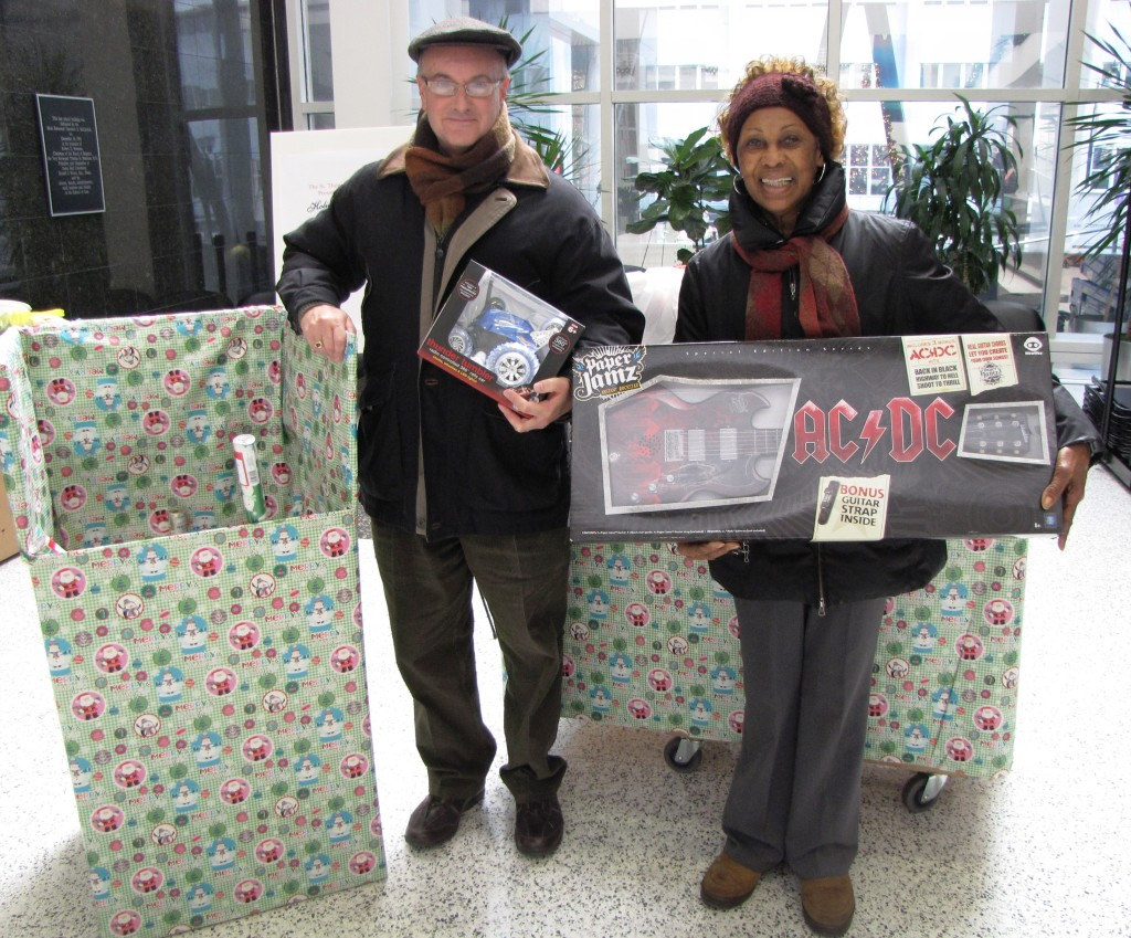 The Rev. Nicholas Gengaro, left, chaplain at Seton Hall University School of Law, displays about $3,000 worth of toys and gifts collected by SHU law students next to NCC Board Member Madge Wilson, who heads the annual toy drive.