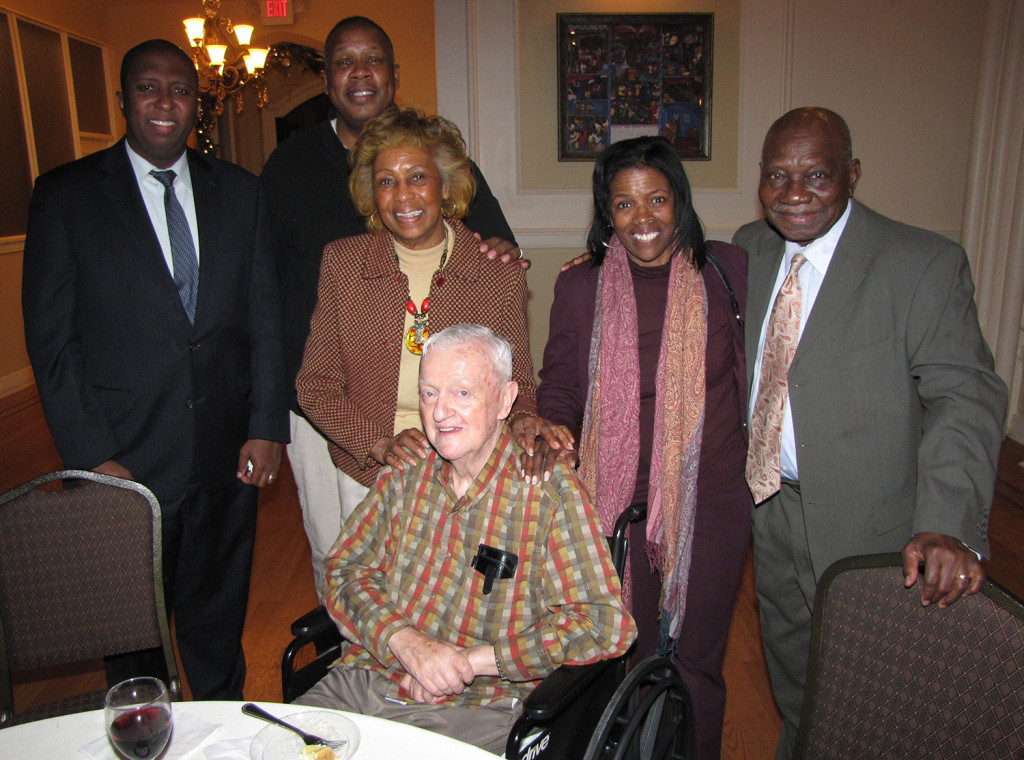 Board members, from left: Edgar Nemorin, Barry Baker, Madge Wilson, NCC Founder and Board Chairman Monsignor William J. Linder, Director of Property Management Fonda Porter, and Dr. A. Zachary Yamba gather for a holiday party at St. Joseph Plaza.