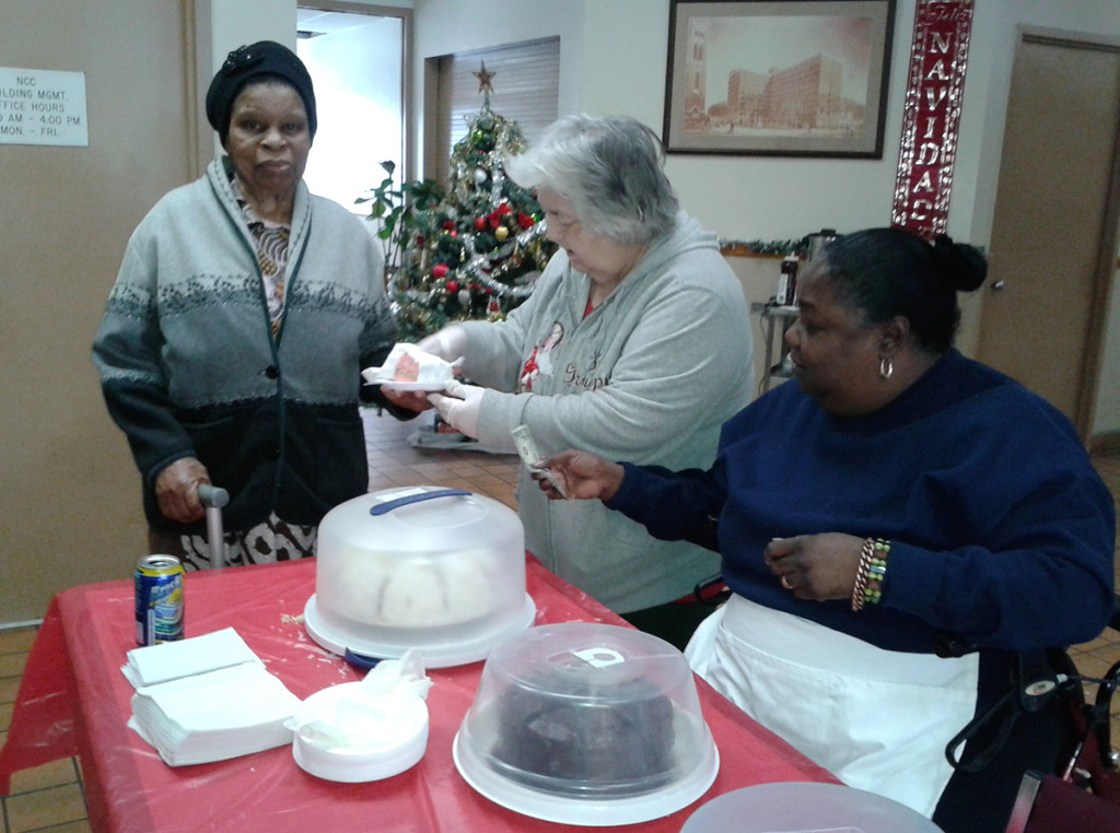 Manor Senior resident Doris Okaro, far left, purchases a slice of cake from Patricia Hulon, center, as Cynthia Sears, right, hands her change. The bake sale raised money for the Manor Senior Tenant Association, of which Sears is the President. Photo courtesy of Sister Mary Prisca.