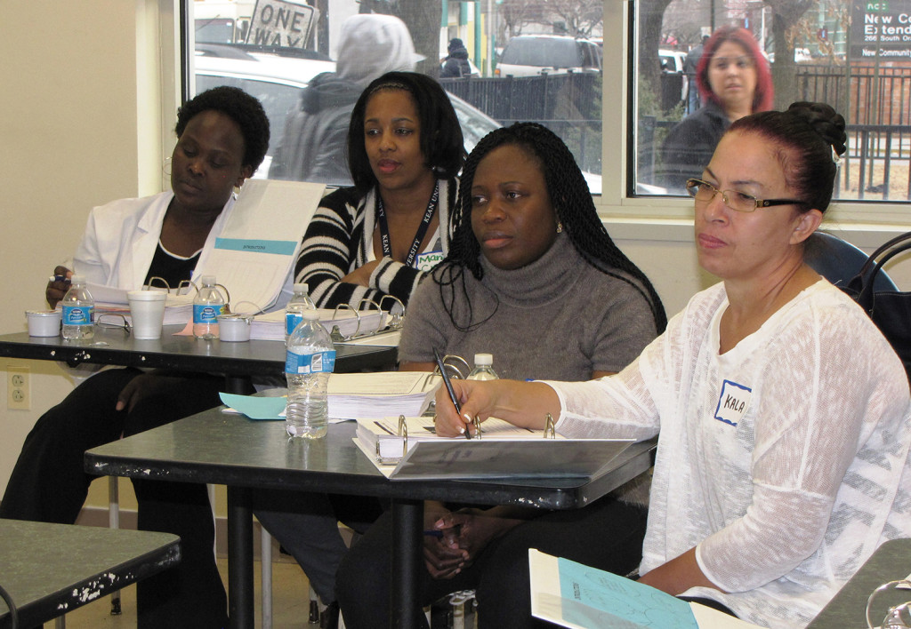 Staff from the New Community Extended Care Facility listen and take notes during a health literacy program held at the Family Service Bureau.