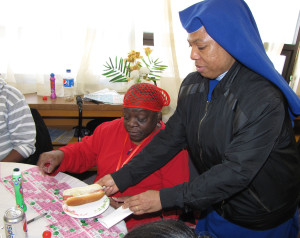 Care Coordinator Sister Mary Prisca, right, serves a hot dog to a senior. Attendees ordered off a menu that included hot dogs with toppings such as chili and cheese, onions, and sauerkraut, chips, drinks and desserts of apple pie and pound cake.