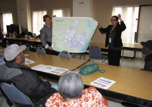 Joyce Sagi, left, and Tess Tomasi, right, of Disaster and Risk Associates, display a Hurricane Sandy flood map of the city of Newark to residents of Gardens Senior.