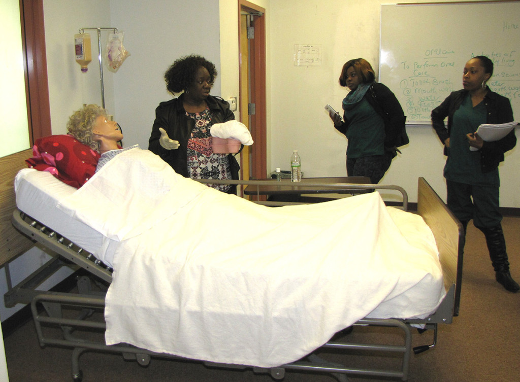 Instructor Tejumade V. Falae, standing left, demonstrates oral hygiene on a patient mannequin as students in the Homemaker Home Health Aide class observe.
