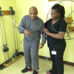 Kenneth Watson, left, practices on the bilateral pulleys with Physical Therapist Assistant Toa Zoko.