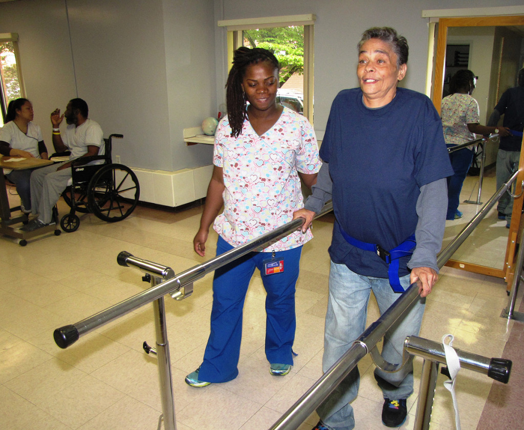 Armenter Hill, right, a resident of New Community Extended Care Facility, supports herself on the parallel bars as she works on building up her leg strength. The mirror at the far end of the parallel bars provides both the resident and therapist with visual feedback on the quality of the gait movement.