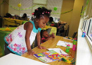 Destiny, foreground, age 2, and her younger sister, Ebony, age 1, colored pictures while attending the event with their mother, Tamara White, not pictured.
