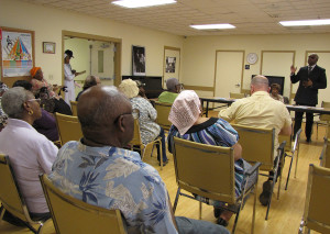 Rodd Henson, standing, of the firm Bermudez Henson, spoke to residents of New Community Orange Senior about Medicare and Medicaid.