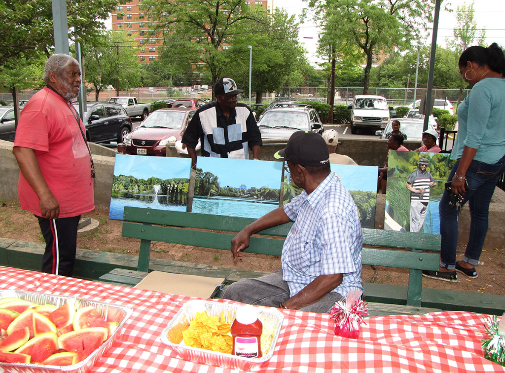 New Community Gardens Senior hosted a backyard barbecue at 265 Morris Ave. in Newark. Resident John Aytch, far left, puts his paintings on display.