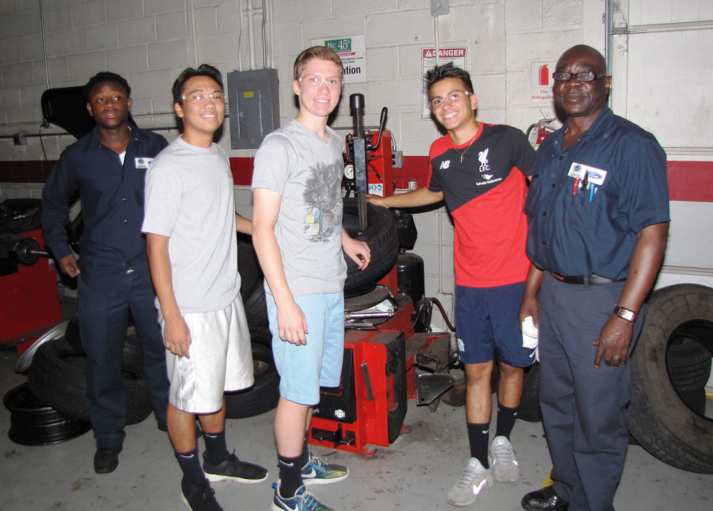 Students from St. Peter's Prep learned how to change tires at the NCC Automotive Training Center, with instruction from John Zaccheus, far right, automotive instructor.
