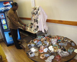 Angela Hall, youth coordinator at Harmony House, organizes the earrings and rings on display.