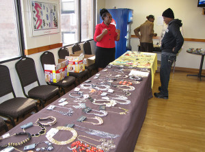 Case Manager Rachel Manyange, left, oversees a table display of jewelry.