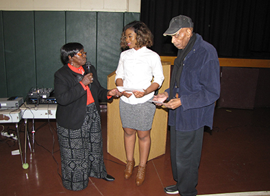 Senior Advisory Board officers Lillie Rivers, left, and Larry Coley, right, present high school senior Sonnie Sorsor, center, with a scholarship.