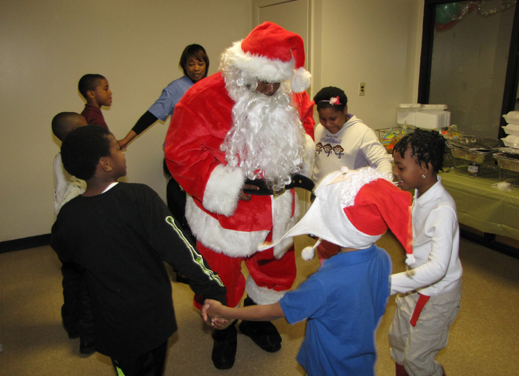Santa Claus dances with the children whose families reside at New Community Sussex Gardens.