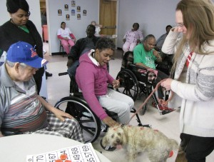 Residents of the New Community Extended Care Facility put their game of bingo on pause to greet Rocky.