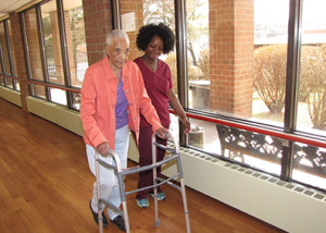 Toa Zoko, right, assists Extended Care resident Elizabeth Hairston during a session of rehabilitation therapy.