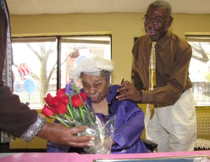 Food Service Director Jackie Henry, left, hands red long-stemmed roses to Edna Van Dunk, who celebrated her 100th birthday at New Community Extended Care Facility.