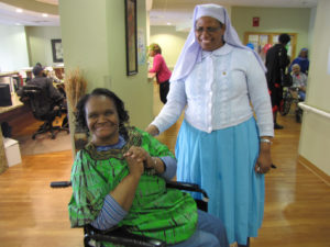 Keisha Buie, left, dons a green dress that she received as a gift from Care Coordinator Sister Theresia Hhayuma.