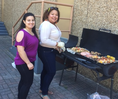 Care Coordinator Luz Toro, right, grills for a barbecue for residents at New Community Douglas Homes.