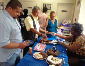 Carol Morris, seated right, serves desserts from a spread of several types of cakes and bread pudding.