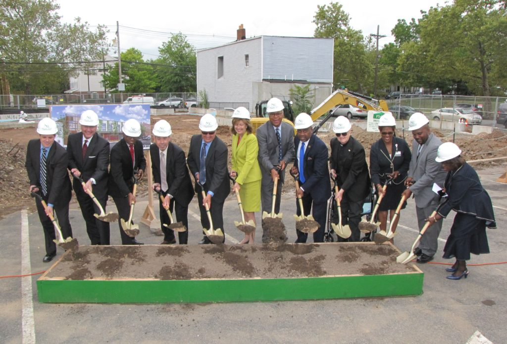 Officials and community leaders gathered at New Community Corporation in Newark and broke ground on A Better Life on September 28, 2016. From left: George Serio, director of the Essex County Division of Housing and Community Development; James Robertson, chief of Legal and Regulatory Affairs, New Jersey Housing and Mortgage Finance Agency; Baye Adofo-Wilson, deputy mayor for Economic and Housing Development, City of Newark; Julio Colon, director of the Department of Housing Assistance, City of Newark; Richard Rohrman, CEO of New Community; Rosemarie Rosati, COO of Rutgers University Behavioral Health Care; Richard Roberts, managing director of Acquisitions at Red Stone Equity Partners; Mayor Ras Baraka, City of Newark; Monsignor William J. Linder, founder and board chair of New Community; Stephanie Welch, program assistant at University Hospital Public Affairs; Thaddaeus L. Diggs, director of Government Relations, Office of General Counsel at University Hospital; Mildred Crump, council president, City of Newark.