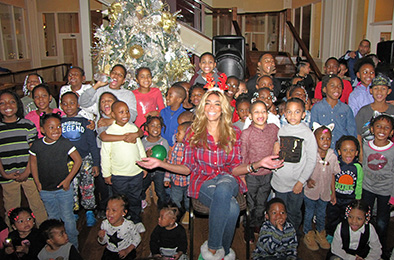 Talk show host Wendy Williams, seated center, shares a moment with children from New Community.