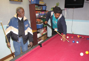 Maurice Okereke, right, activity assistant at New Community Extended Care Facility, shoots a game of pool with resident Lee L. Burgman, left.
