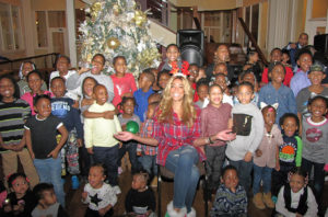 Wendy Williams, seated center, surrounded by children from New Community Harmony House, early learning centers and programs during the Hunter Foundation's holiday dinner hosted at St. Joseph Plaza on Dec. 7, 2016.