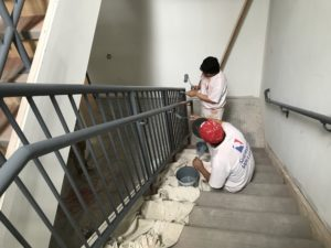 Workers paint a railing inside New Community's new housing facility for the chronically homeless, A Better Life.