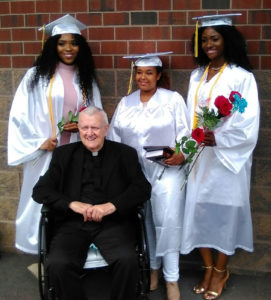 Monsignor William J. Linder poses with scholarship recipients Chikama Onwunaka, Sibonai Ruthie Geberyesus and Maryana Okoye (left to right) who received their diplomas from Saint Vincent Academy June 4. Photo courtesy of Madge Wilson.