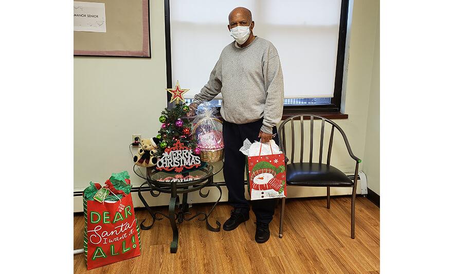 Manor Senior Christmas Presents Man Holding Bag for Website