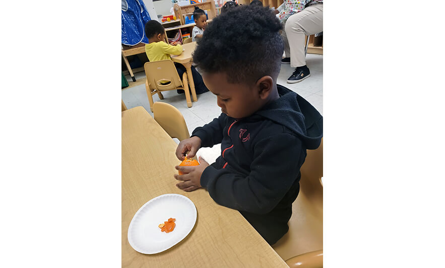 HHELC Week of the Young Child 2021 Boy Peeling Orange for Web