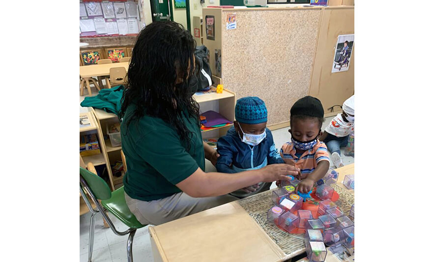 HHELC Week of the Young Child 2021 Teacher Helping Boys with Blocks for Web