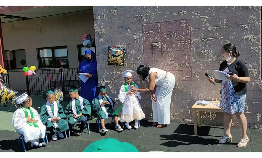 HHELC Moving On Ceremony 2021 Teacher Holding Microphone for Girl Standing for Web